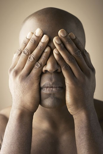 Close-up of a young man covering his eyes with his hands : Stock Photo