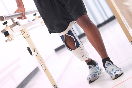 Stock Photo: 1525R-14158 Low section view of a patient walking with the help of parallel bars