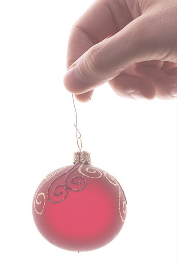Stock Photo: 1525R-14671 Hand holding red Christmas ornament