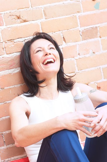 Mature adult woman laughing with water bottle  : Stock Photo