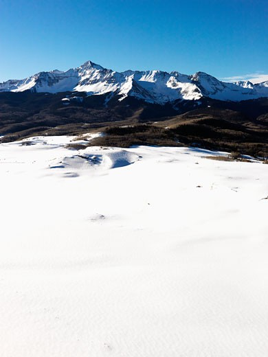 Aerial landscape of Colorado Rockies with snow covered valley in foreground. : Stock Photo
