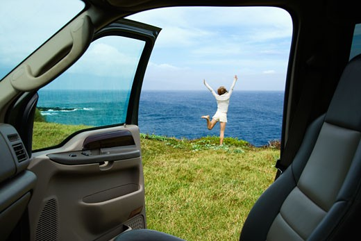 Excited woman standing on grassy cliff by Pacific Ocean in Maui, Hawaii. : Stock Photo