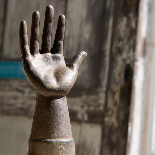 Stock Photo: 1525R-151794 Metal statue of hand against wooden background.