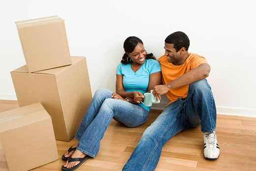 African American male and female couple sitting on floor next to moving boxes relaxing. : Stock Photo