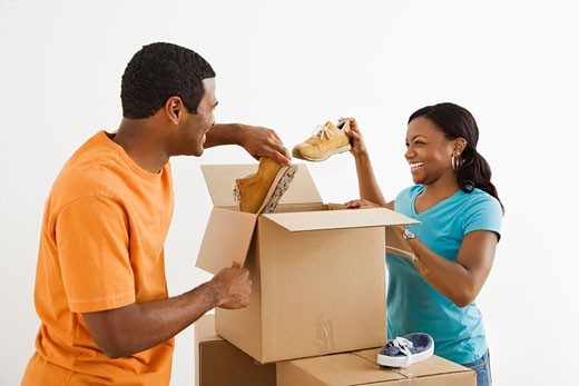 African American male and female couple packing cardboard boxes with shoes. : Stock Photo