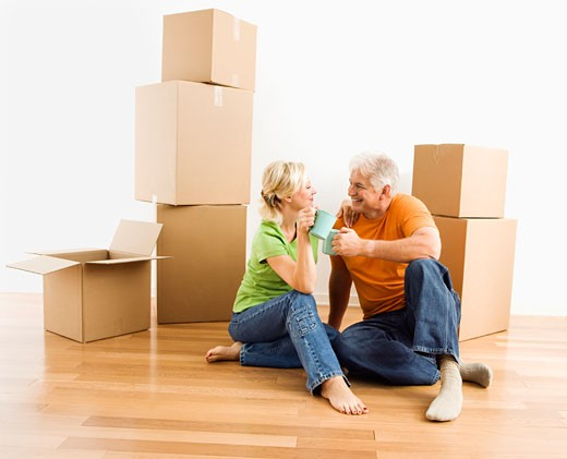 Middle-aged couple sitting on floor among cardboard moving boxes drinking coffee. : Stock Photo