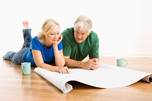 Stock Photo: 1525R-152088 Middle-aged couple lying on floor looking at architectural blueprints together.