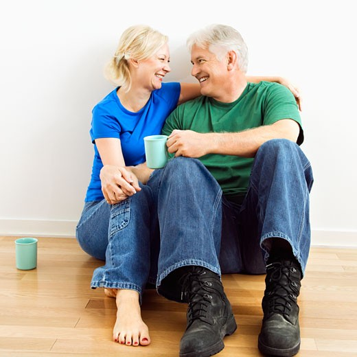 Middle-aged couple sitting on floor snuggling and drinking coffee. : Stock Photo