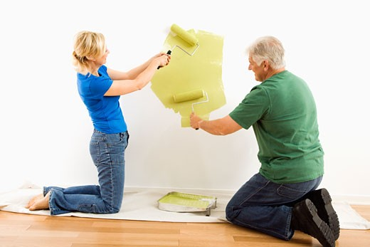 Middle-aged couple beginning to paint wall green over drop cloth. : Stock Photo