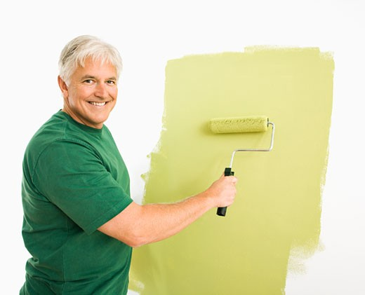 Middle-aged man painting wall green with paint roller smiling at viewer. : Stock Photo