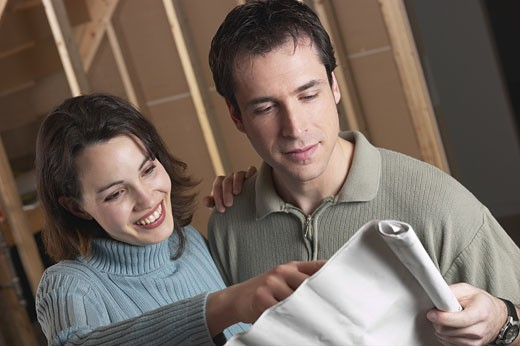 Adult couple looking at blue prints  : Stock Photo