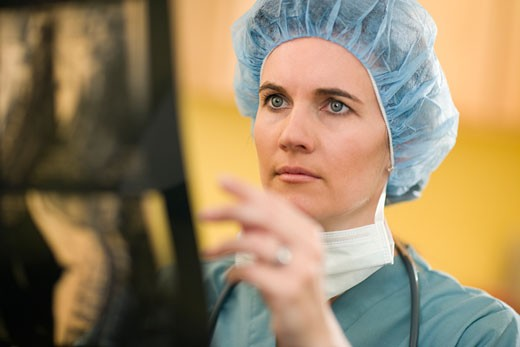Serious woman doctor analyzing X-rays : Stock Photo