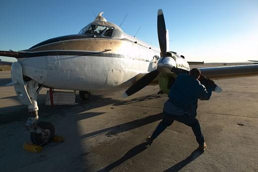 Mechanic pulling on propeller  : Stock Photo