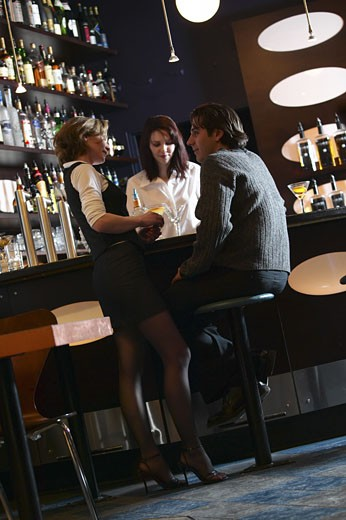 Young couple being served by bartender at mahogany bar : Stock Photo