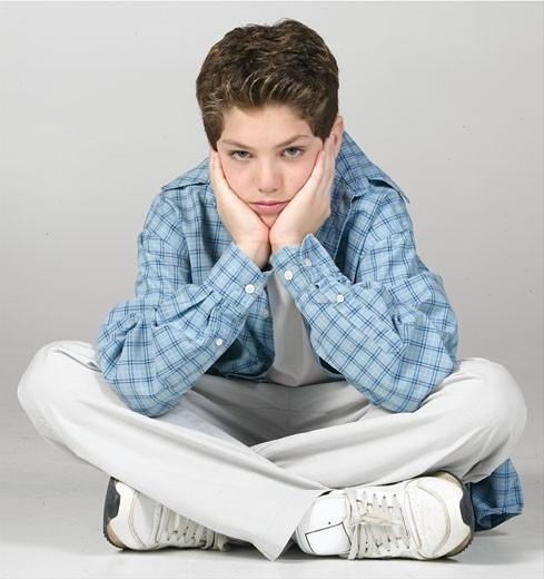 Stock Photo: 1525R-16664 Bored teenager sitting cross-legged