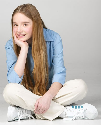 Smiling teenaged girl sitting cross-legged : Stock Photo