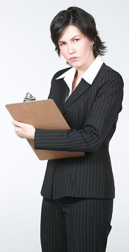 Serious businesswoman in suit writing on clipboard : Stock Photo