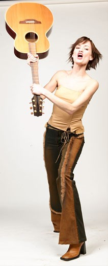 Stock Photo: 1525R-16887 Woman swinging acoustic guitar over her head