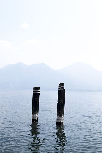 Stock Photo: 1525R-17024 Rotting dock posts in misty mountain-lined lake