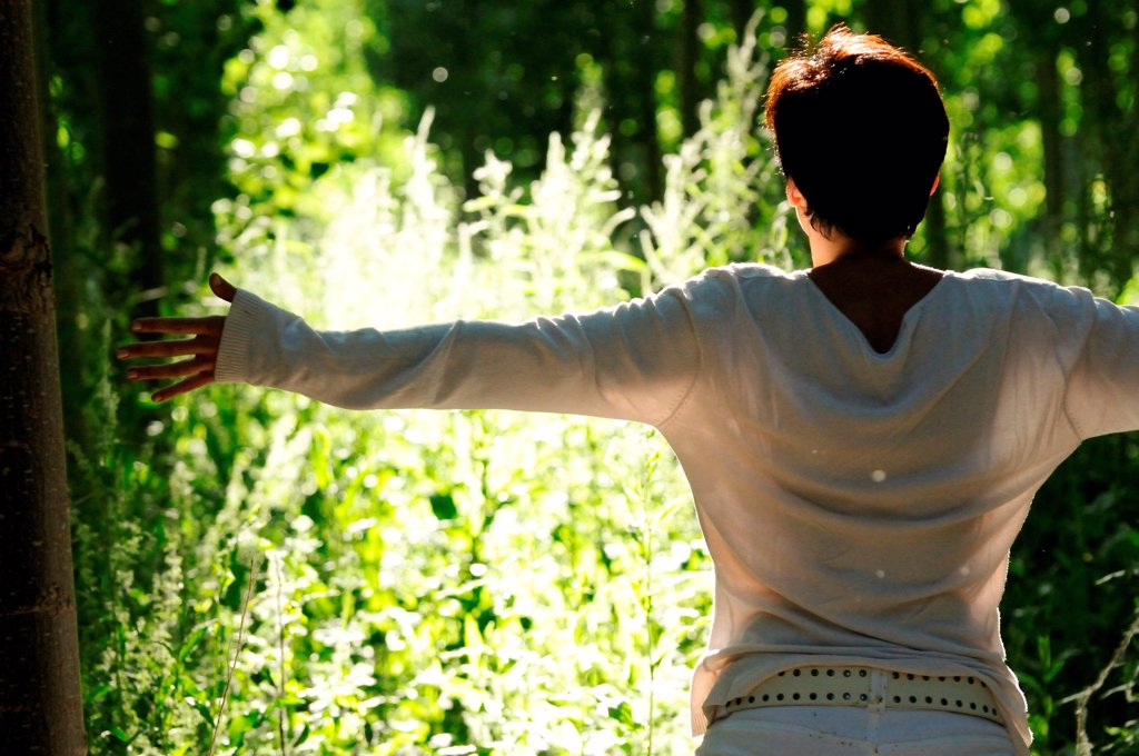 Stock Photo: 1525R-190978 Woman with arms out stretched in green woodland