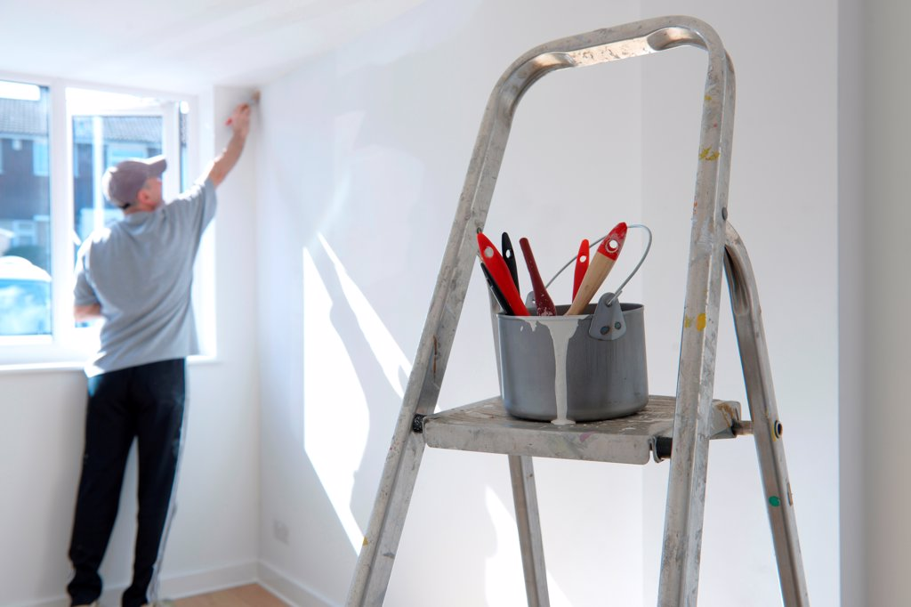 Stock Photo: 1525R-190981 man decorating a room with ladder and paint pot in foreground
