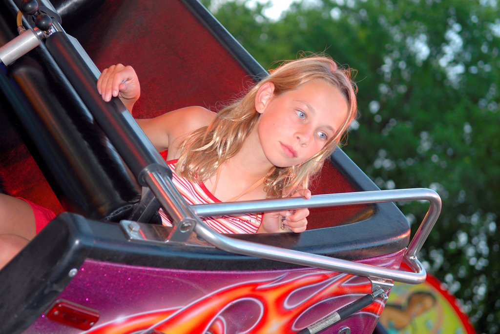 Stock Photo: 1525R-191576 Girl alone on fairground ride