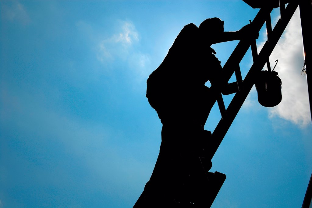 Stock Photo: 1525R-191609 Silhouette of man climbing ladder to paint building