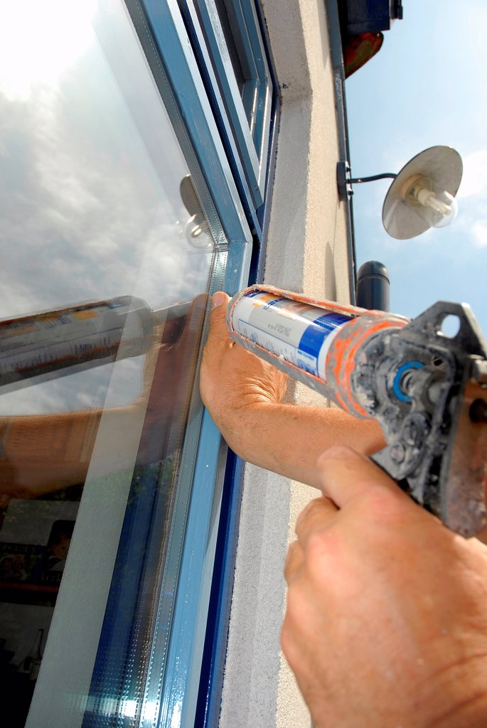 Stock Photo: 1525R-191621 Close-up of man adding adhesive to window