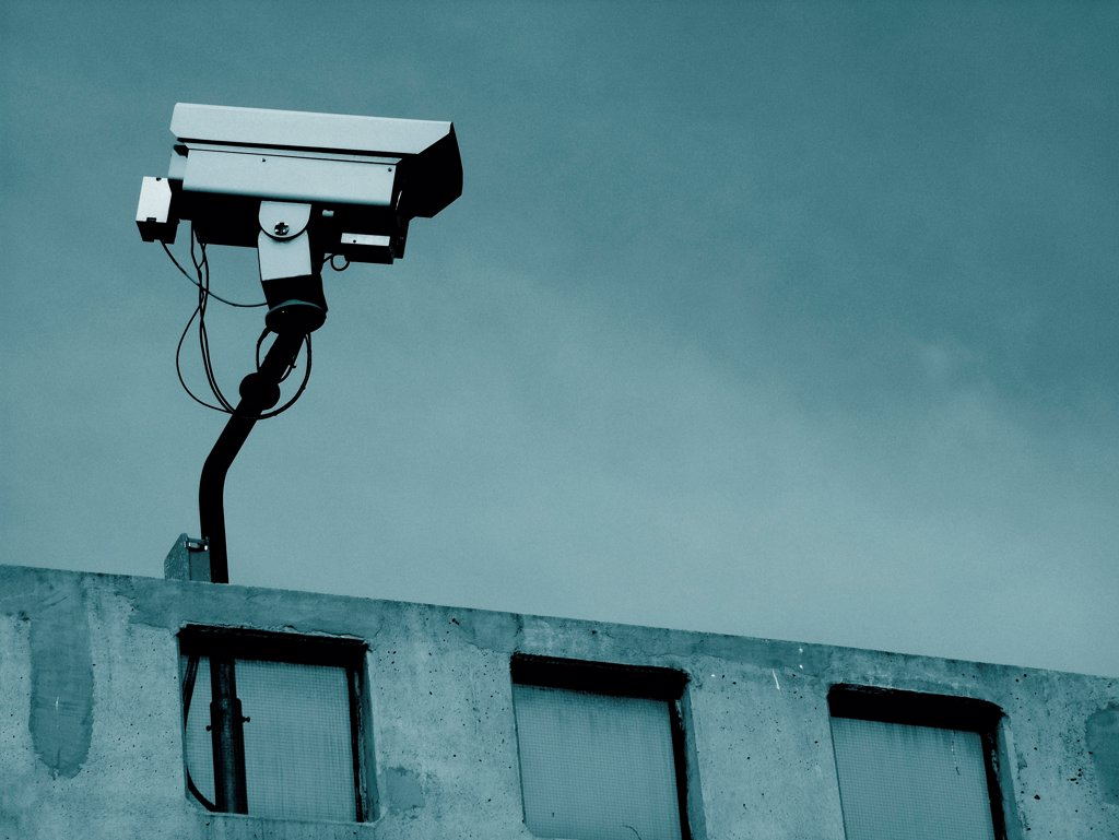 Stock Photo: 1525R-192324 Security surveillance camera on rooftop of urban building.