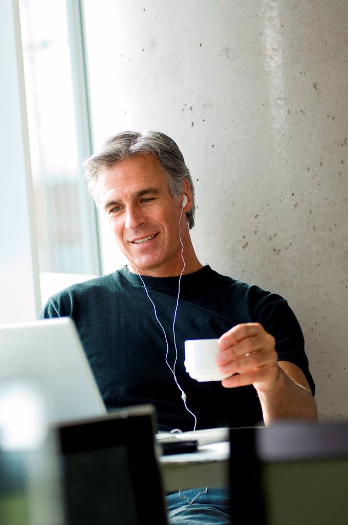 Stock Photo: 1525R-192695 Middle-aged man listening to music in urban cafe.