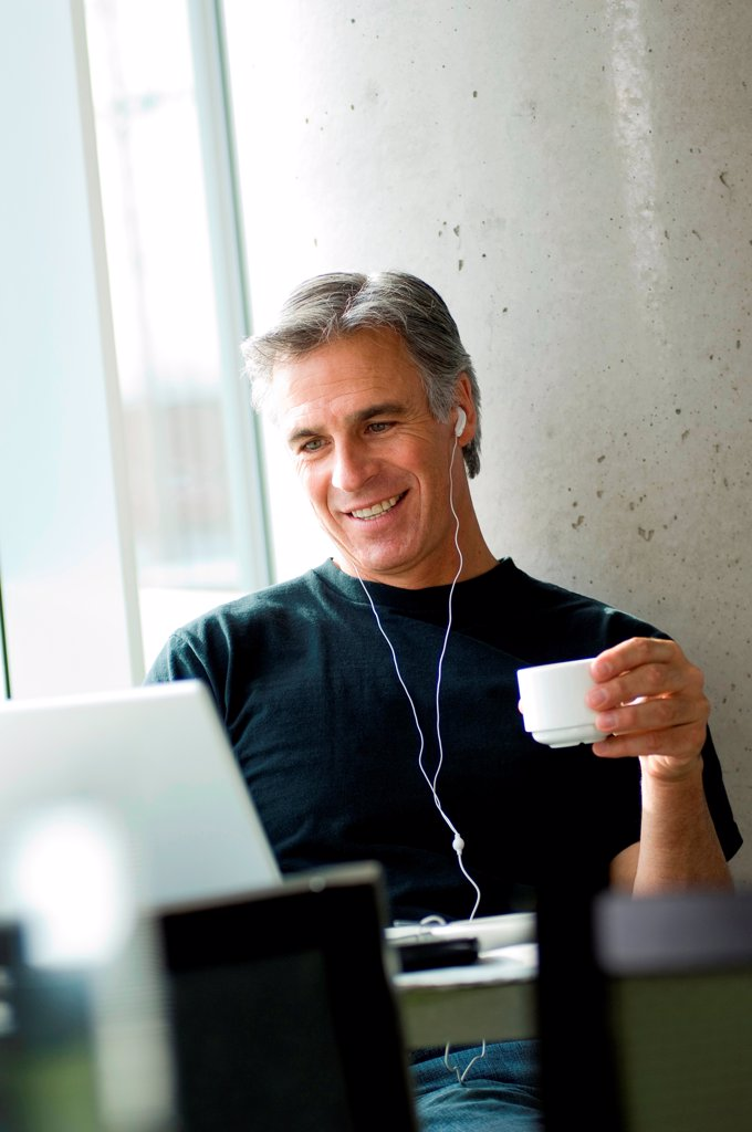 Stock Photo: 1525R-192696 Middle-aged man listening to music in urban cafe.