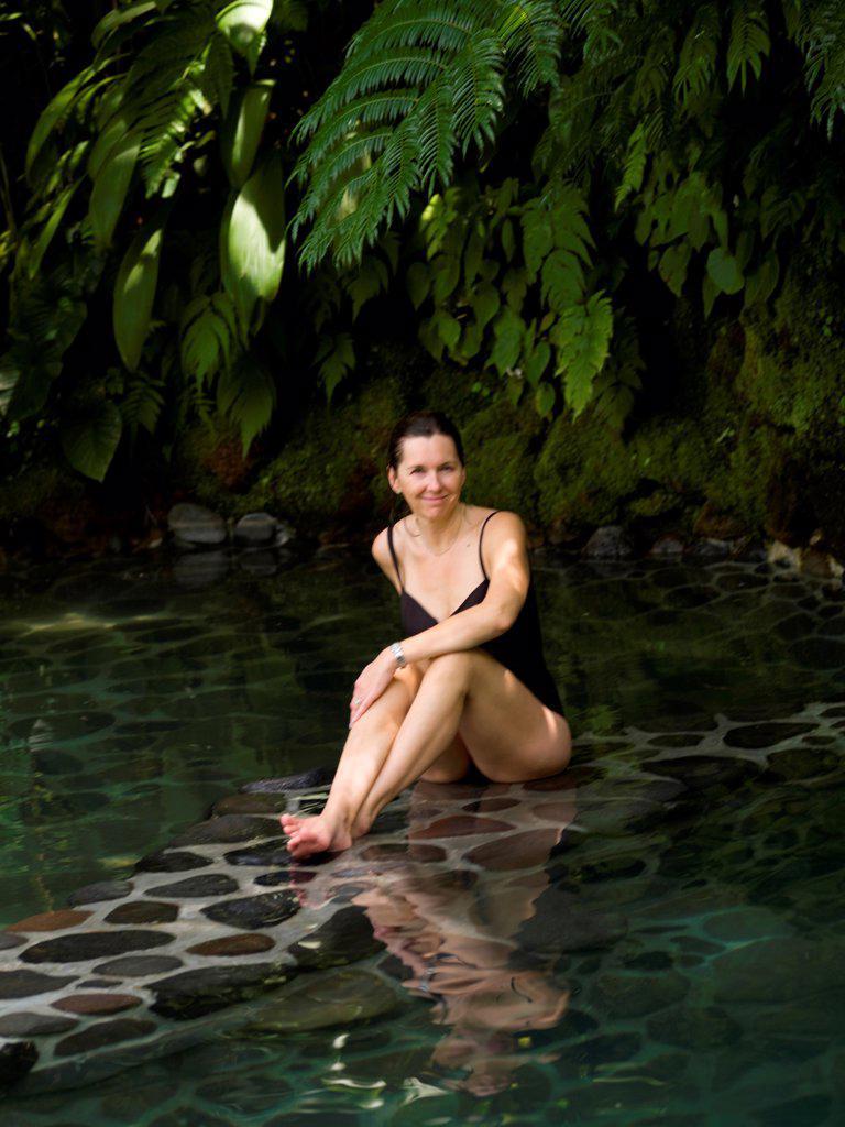 Stock Photo: 1525R-195042 Caucasian woman sitting on edge of pool in Bali