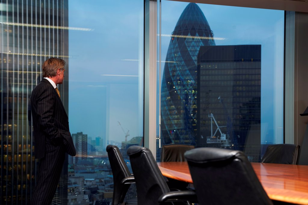 Stock Photo: 1525R-202700 Senior business man standing in boardroom alone looking out of window of view of city