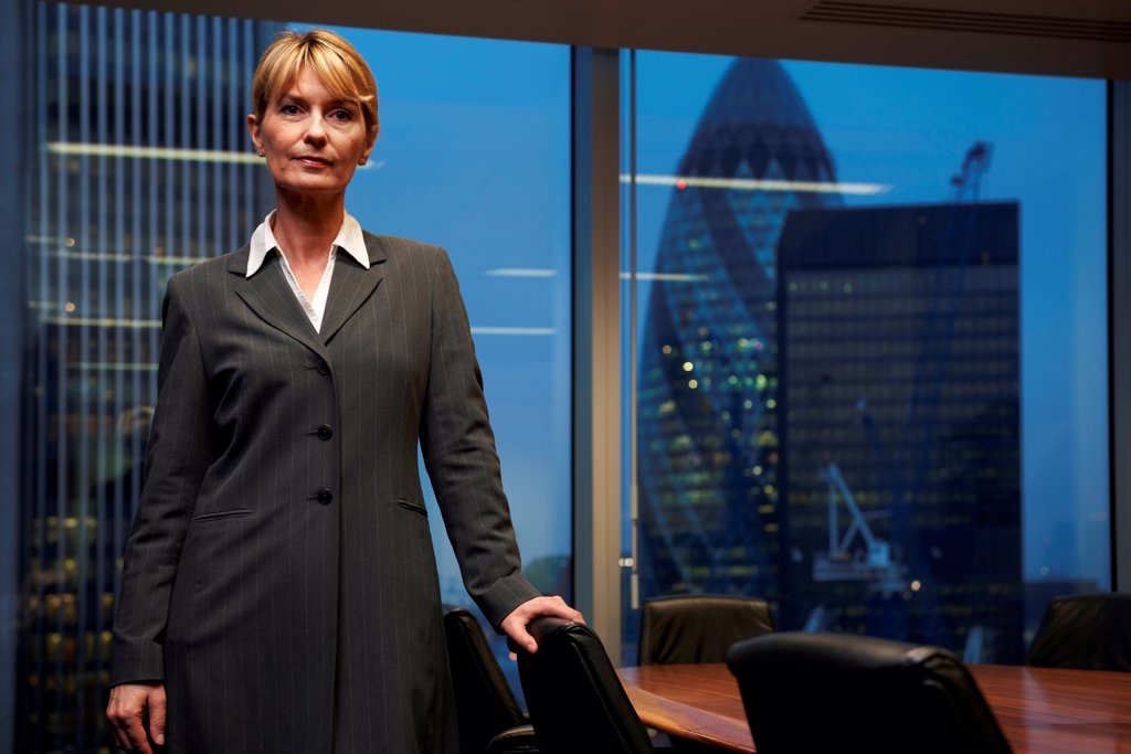 Serious Business woman leaning on chair in boardroom looking at camera : Stock Photo
