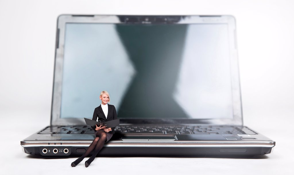 Young businesswoman sitting on a laptop, isolated on white : Stock Photo