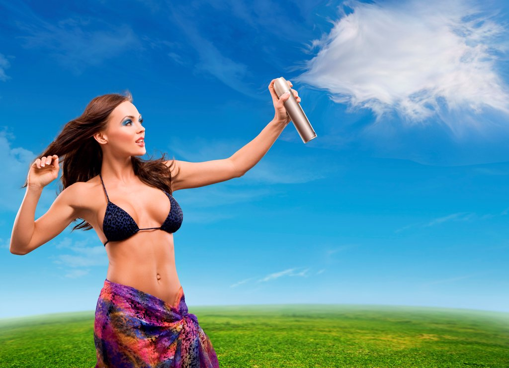 Young beautiful woman sprays clouds on a sunny day : Stock Photo