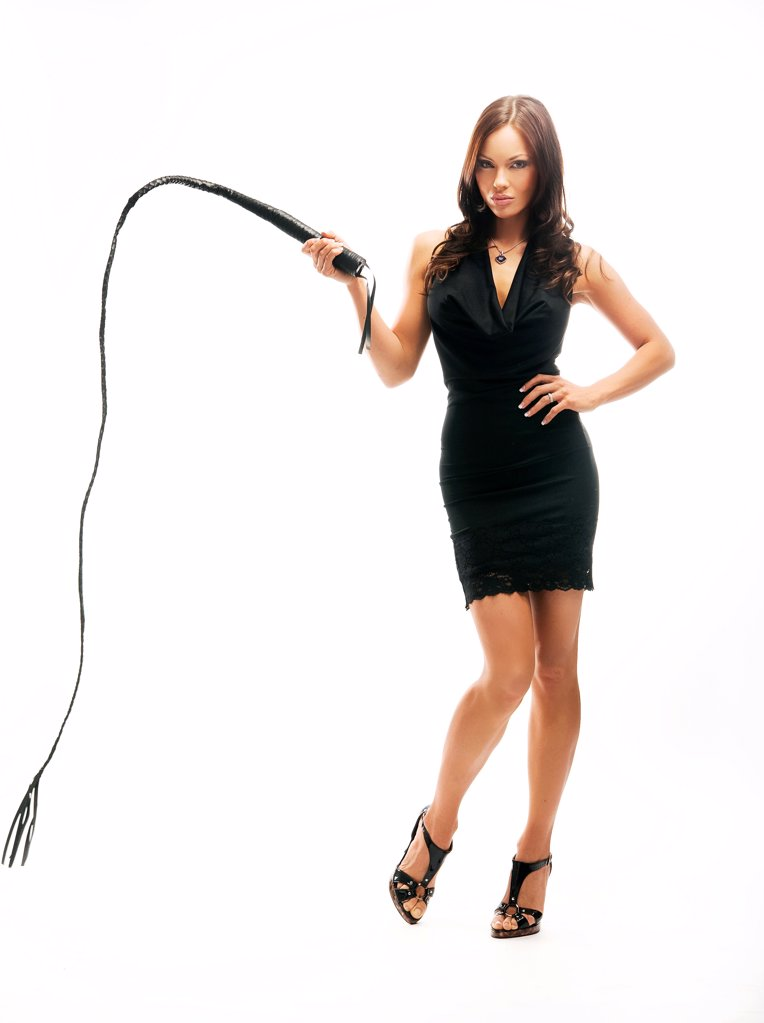 Dominant sexy lady holding a whip, isolated on white : Stock Photo