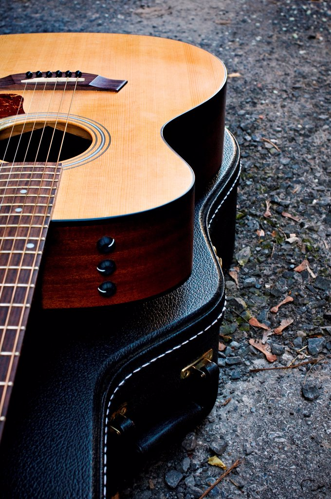 Acoustic guitar sitting on it's closed case. : Stock Photo