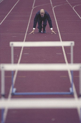 suited man on starting blocks of hurdle running track : Stock Photo
