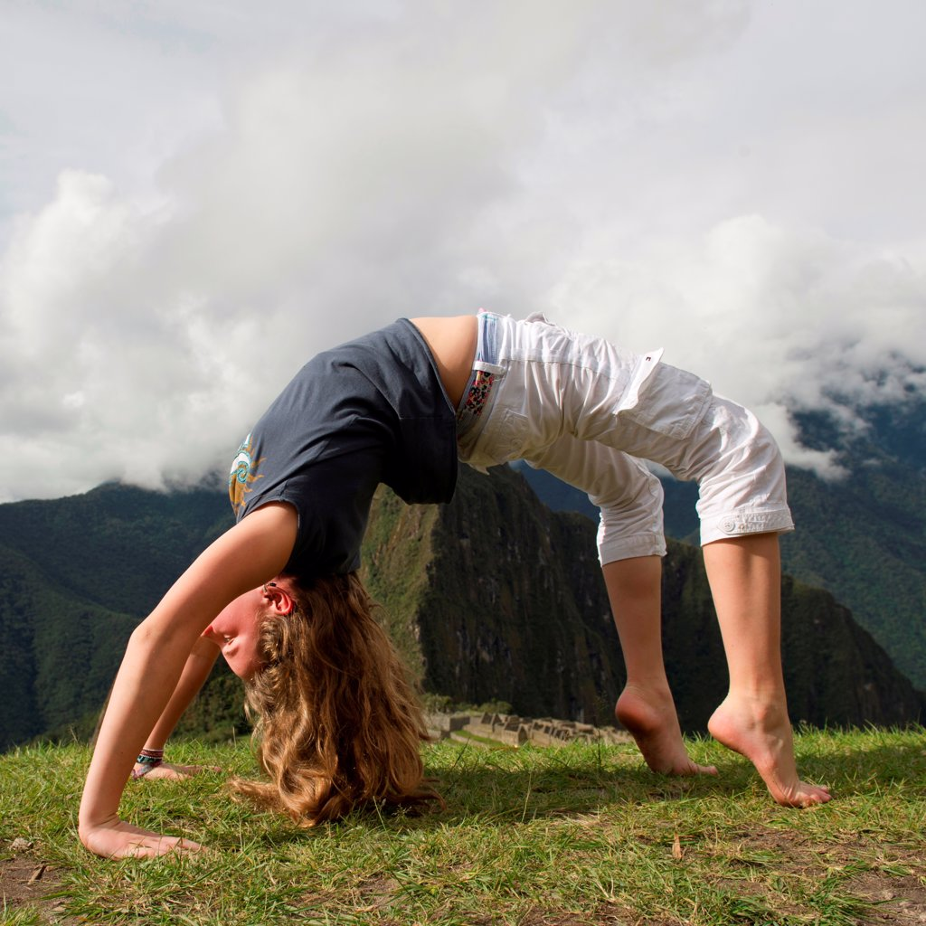 Stock Photo: 1525R-207917 Teenage girl doing wheel pose with valley in the background, The Lost City of The Incas, Machu Picchu, Cusco Region, Peru