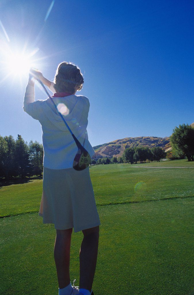 Rear view of a young woman playing golf : Stock Photo