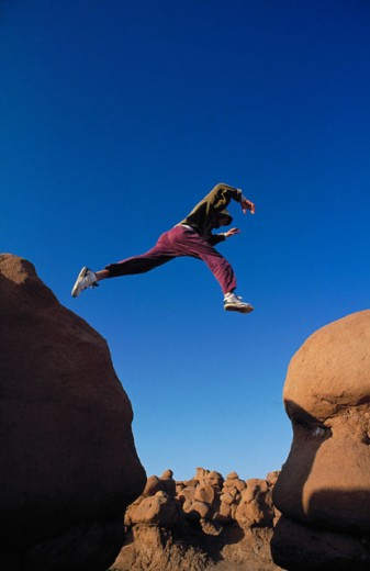 Low angle view of a young man jumping from one rock to another : Stock Photo
