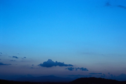 Sparsely Clouded Clear Blue Sky Over Mountains At Dusk : Stock Photo