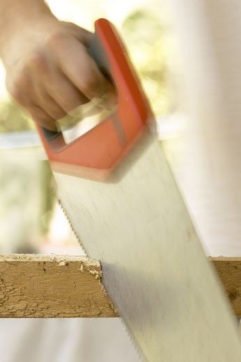Stock Photo: 1525R-3905 Close-up of a man's hand using a hand saw on a piece of wood