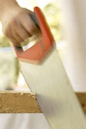 Close-up of a man's hand using a hand saw on a piece of wood : Stock Photo