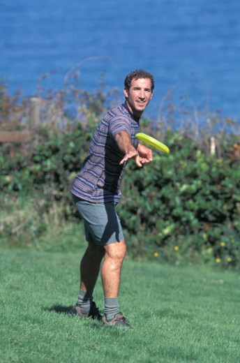 Stock Photo: 1525R-39658 Caucasian Man Playing Frisbee Near A Lake