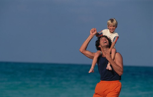 Stock Photo: 1525R-4383 Father carrying his son on his shoulders on the beach