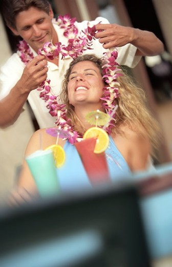 Man Putting Lei Over Woman's Head : Stock Photo