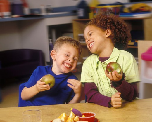 Children Eating Apples And Laughing In Classroom : Stock Photo