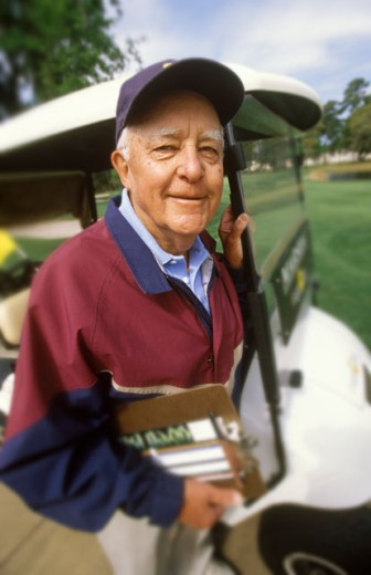 Elderly Man Standing In Front Of Golf Cart And Smiling : Stock Photo